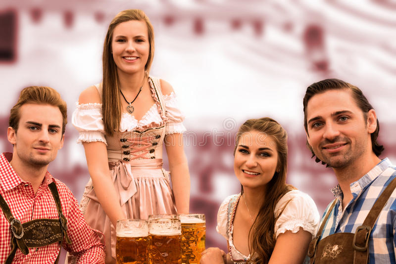 Waitress delivers beers in tent with happy visitors in a beer tent at Munich Oktoberfest. Against blurred red background royalty free stock image