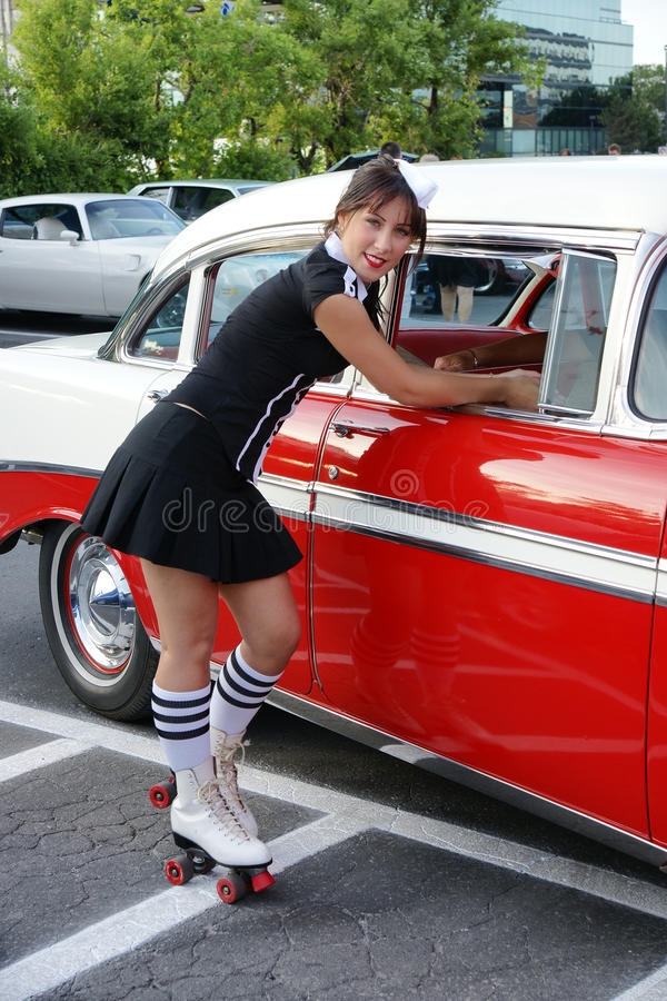 Waitress at drive-in restaurant. Picture of young woman waitress with roller skate an old car royalty free stock image