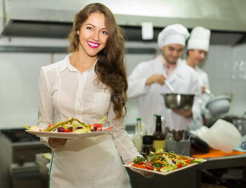 Waitress with food at kitchen royalty free stock image