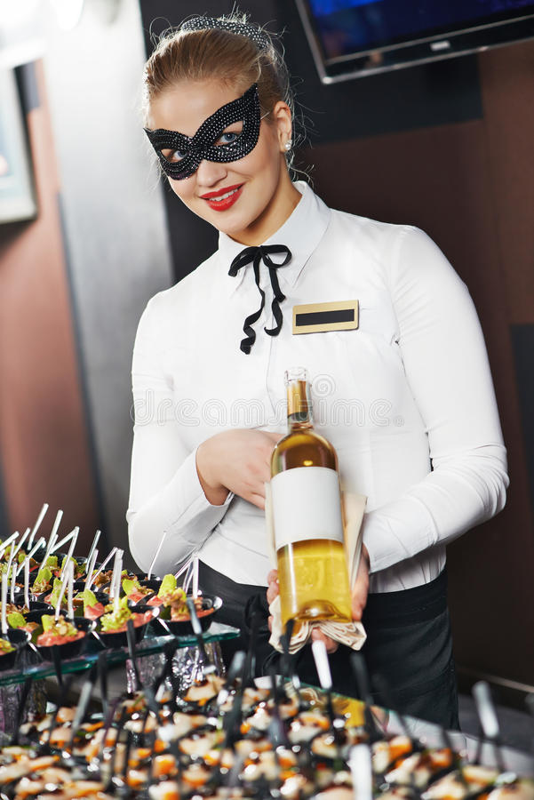 Waitress girl in mask with bottle royalty free stock images