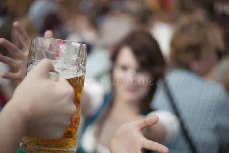 Waitress hands over a beer mug at Oktoberfest stock photo