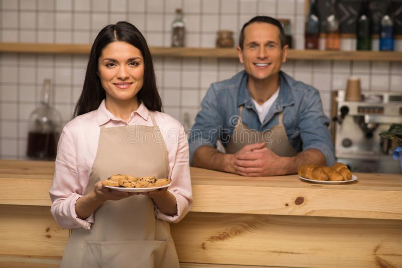 Waitress holding cookies on the plate. Portrait of waitress holding cookies on the plate and looking at camera with waiter on the background stock photos