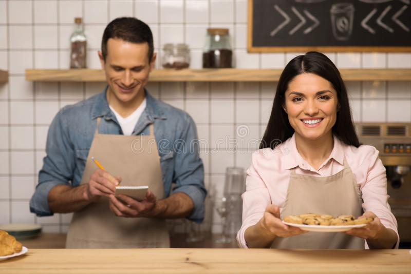 Waitress holding cookies on the plate. And looking at camera while waiter taking notes stock photography