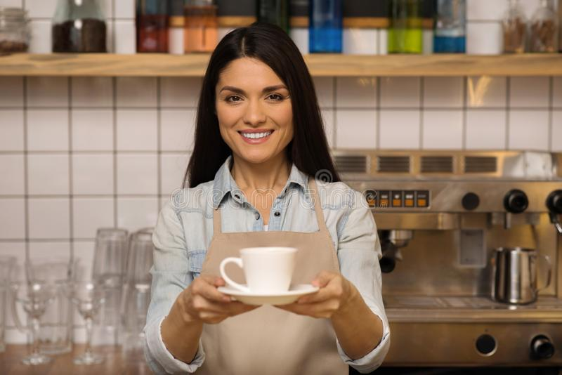 Waitress holding cup of coffee. Portrait of smiling waitress holding cup of coffee and looking at the camera stock photography