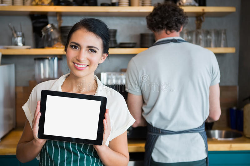 Waitress holding digital tablet while waiter working in background royalty free stock photo