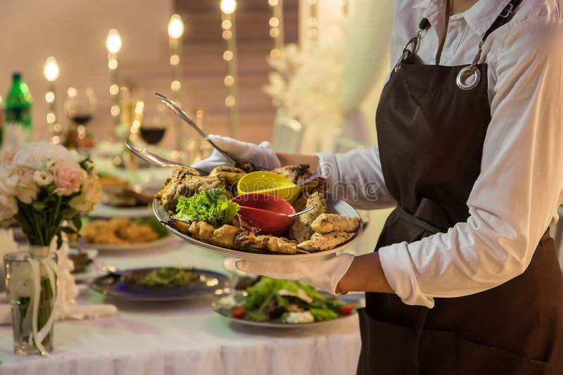 The waitress is holding a dish with chicken kebabs and rolls stock image