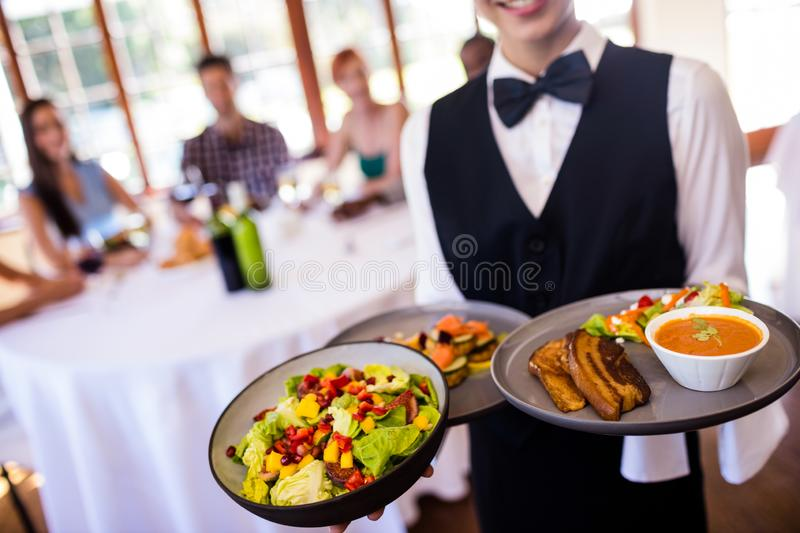 Waitress holding food on plate in restaurant royalty free stock photography