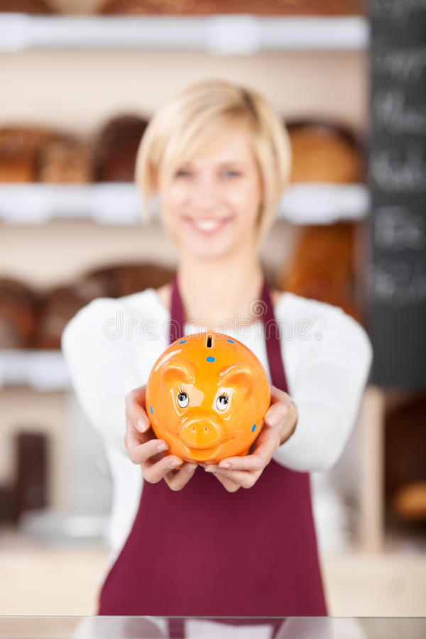 Download Waitress Holding Piggybank At Bakery Counter Stock Photo - Image: 31273660
