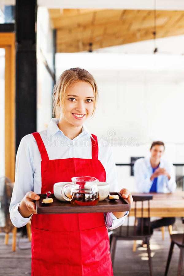 Waitress holding a tray with tea and coffee stock photo