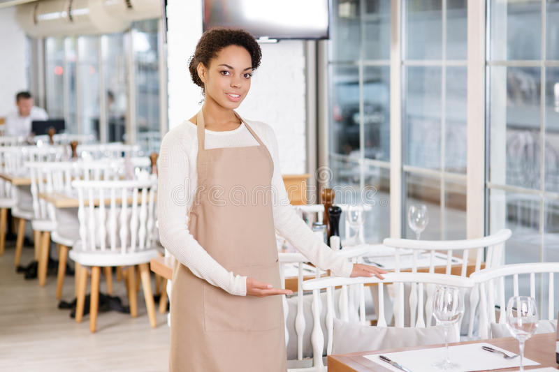 Waitress offering a seat. Polite service. Pleasant young waitress is offering a nice seat to the customer royalty free stock photography