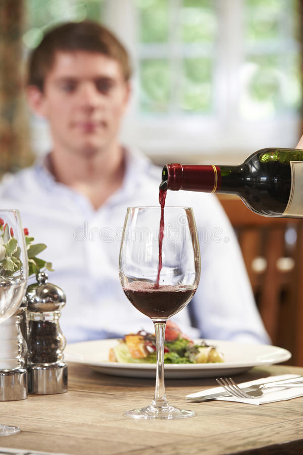 Waitress Pouring Customer Glass Of Red Wine royalty free stock image
