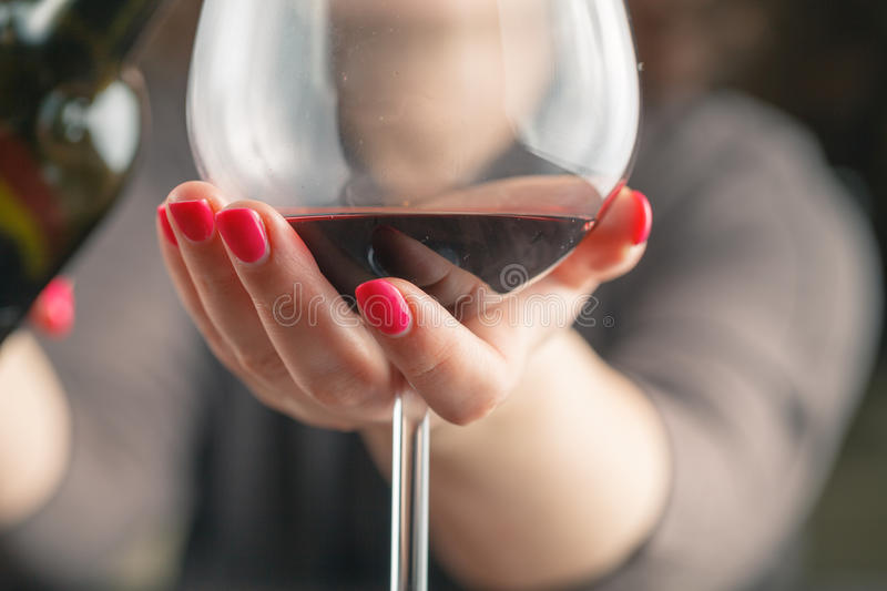 Waitress pouring red wine in a glass royalty free stock image