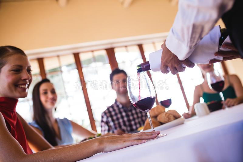 Waitress pouring red wine in wine glass on table royalty free stock image