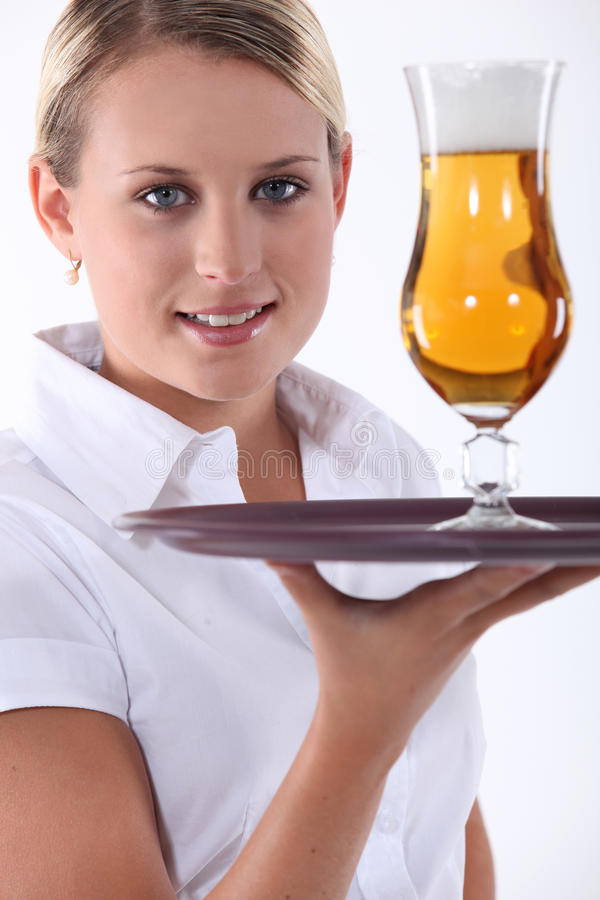 Waitress serving beer. Waitress serving a cold beer royalty free stock image