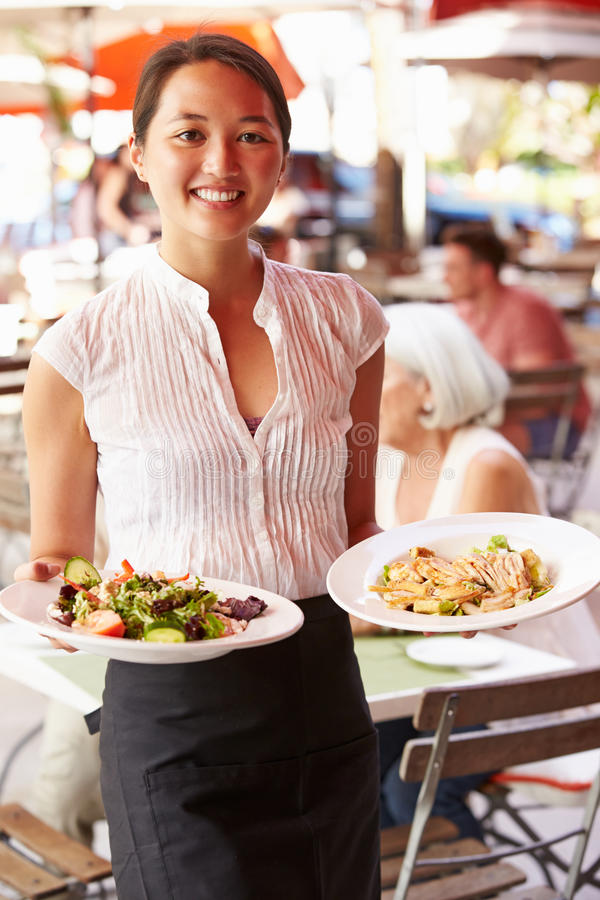 Waitress Serving Food At Outdoor Restaurant stock images