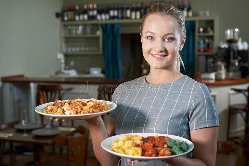 Waitress Serving Plates Of Food In Restaurant stock photo