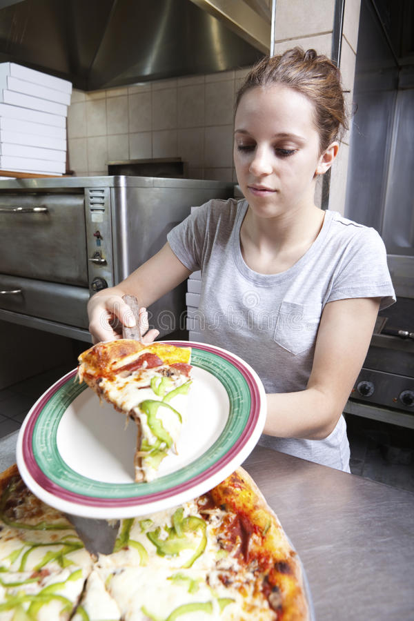 Waitress serving a slice of all dressed pizza.  stock photos