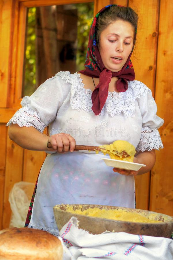 Waitress serving traditional polenta in Transylvania royalty free stock photography
