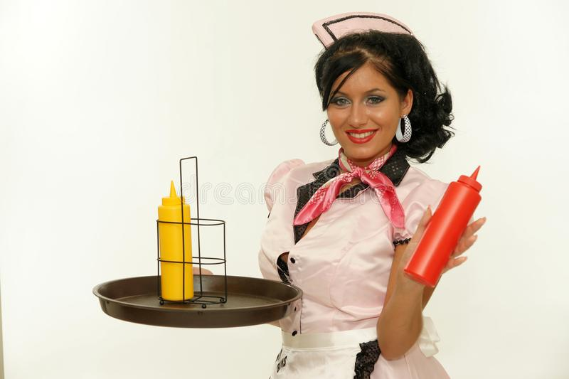 Waitress showing a ketchup bottle stock images