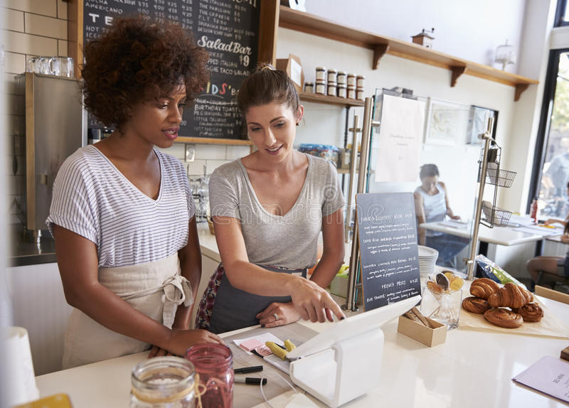 Waitress showing new employee the till at a coffee shop royalty free stock image