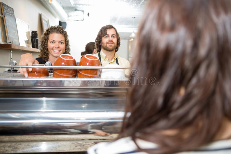 Waitress Standing With Colleague At Coffeeshop stock photos