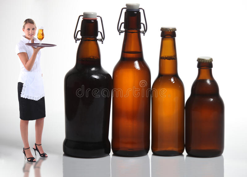 Waitress stood with beer. Bottles stock photography