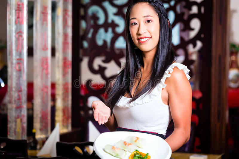 Waitress with sushi in restaurant. Waitress with sushi in asian restaurant stock images