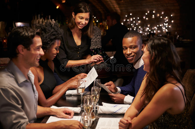 Waitress Takes Order In Restaurant Using Digital Tablet stock photography