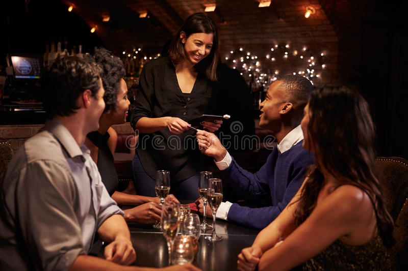 Waitress Takes Payment For Restaurant Bill On Digital Tablet royalty free stock image