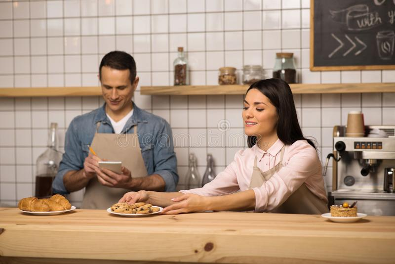 Waitress taking cookies on the plate from table. While waiter taking notes royalty free stock photos