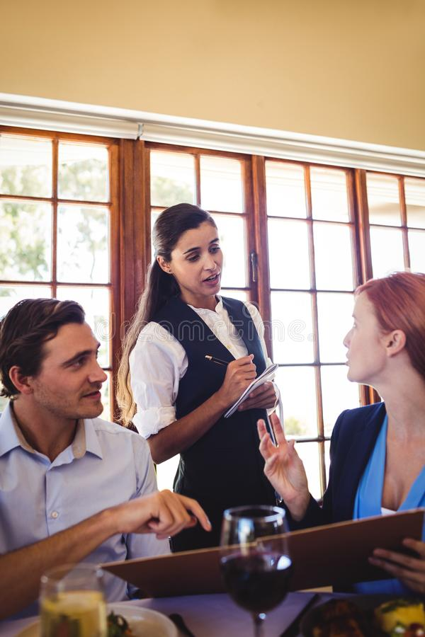 Waitress taking food order from business people stock photo