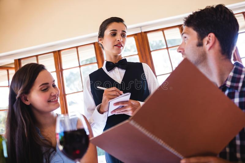 Waitress taking an order from a couple stock image