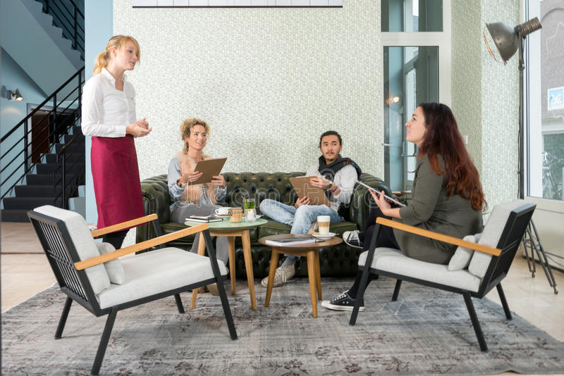 Waitress Taking An Order From Customer In Cafe. Waitress taking an order from female customer while friends looking at her in cafe royalty free stock photos