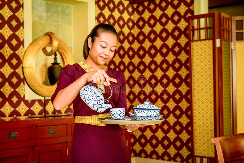 Waitress in the thai restaurant with teapot and cup on the tray stock photos