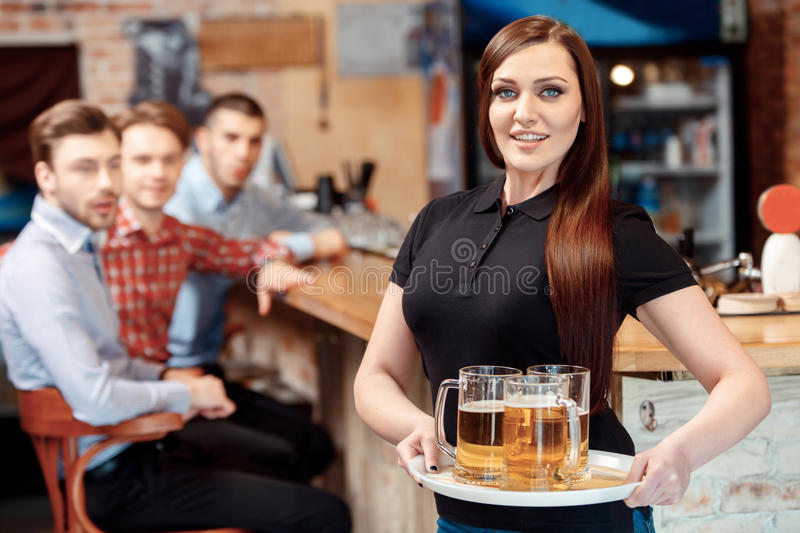 Waitress with a tray of beer. What a beautiful girl. Selective focus on beautiful waitress holding a tray with beer glasses while young men are looking at her royalty free stock photography