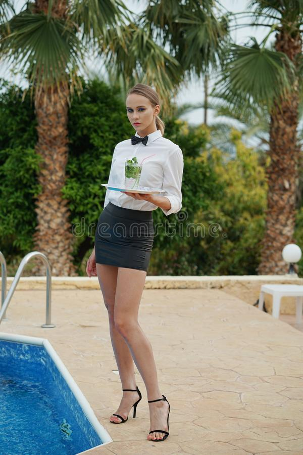 Waitress with tray by the swimming pool stock images