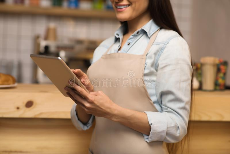 Waitress using digital tablet. Cropped image of smiling waitress using digital tablet in cafe royalty free stock image