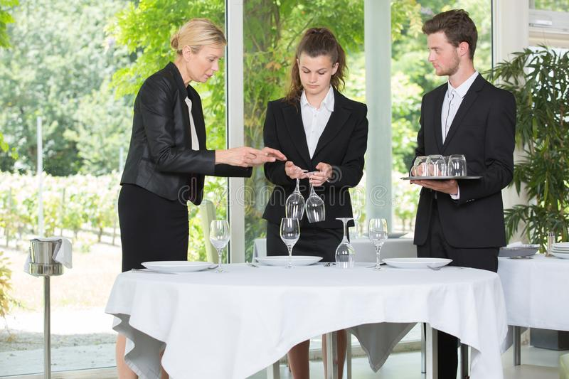 Waitress and waiter cleaning glasses in restaurant. Waitress and waiter cleaning glasses in a restaurant royalty free stock photo