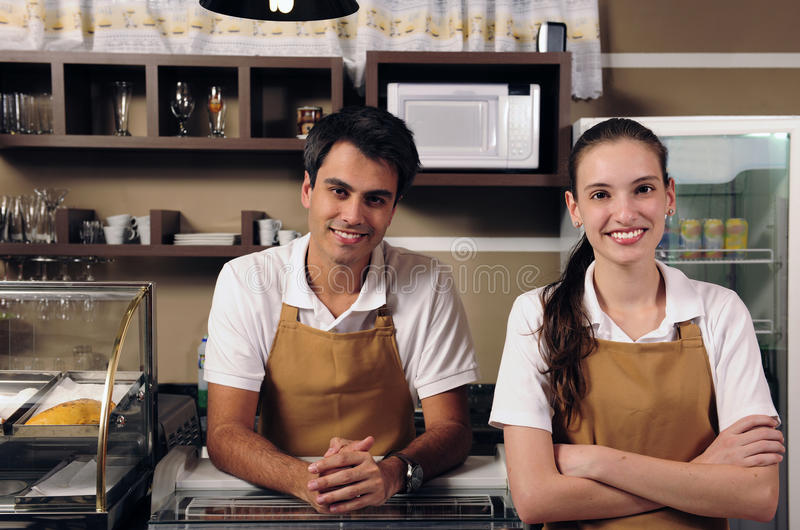 Waitress and waiter working at a cafe. Couple is owner of a cafe or waitress and waiter working royalty free stock photo