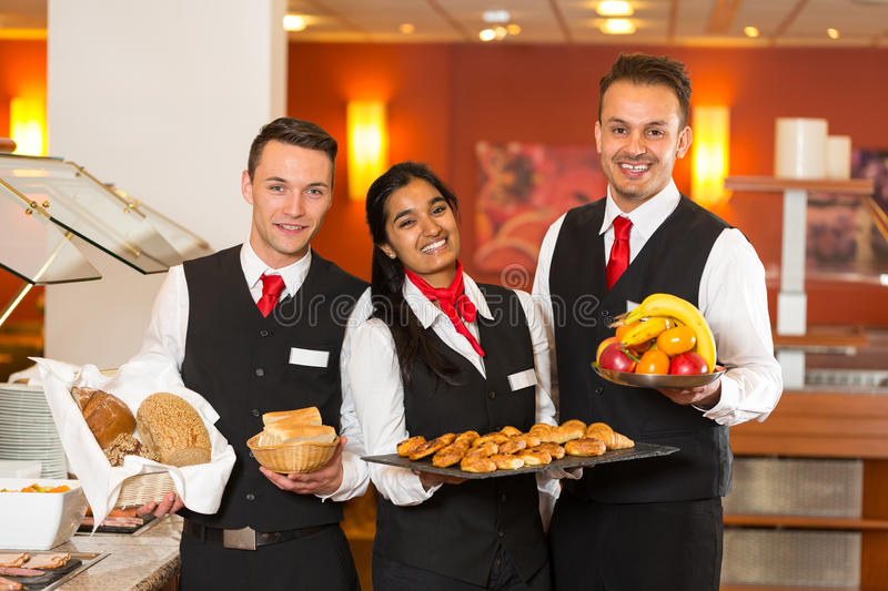Waitress and waiters posing with food at buffet in a restaurant. Waitress and waiters posing with food at buffet in restaurant stock photography
