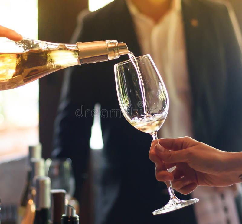 Pouring wine from the bottle into glasses stock image