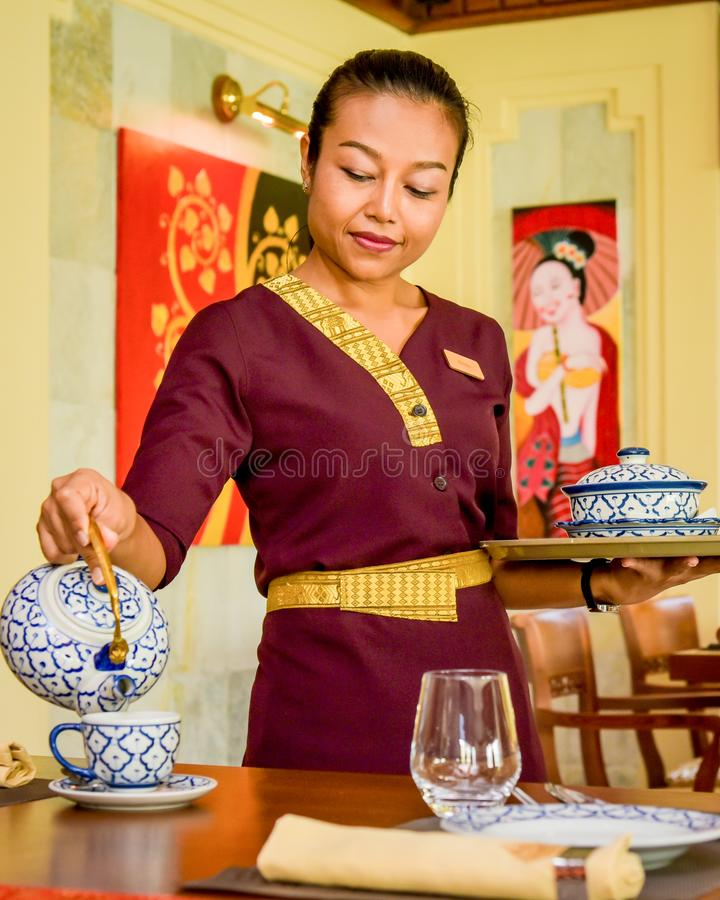 Waitress wearing uniform in the thai restaurant serving tea stock images