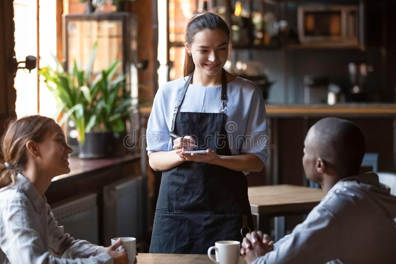 Waitress welcoming restaurant guests take order writing on notepad. Waitress female welcoming diverse cafeteria pub guests african guy mixed race girl making royalty free stock photo
