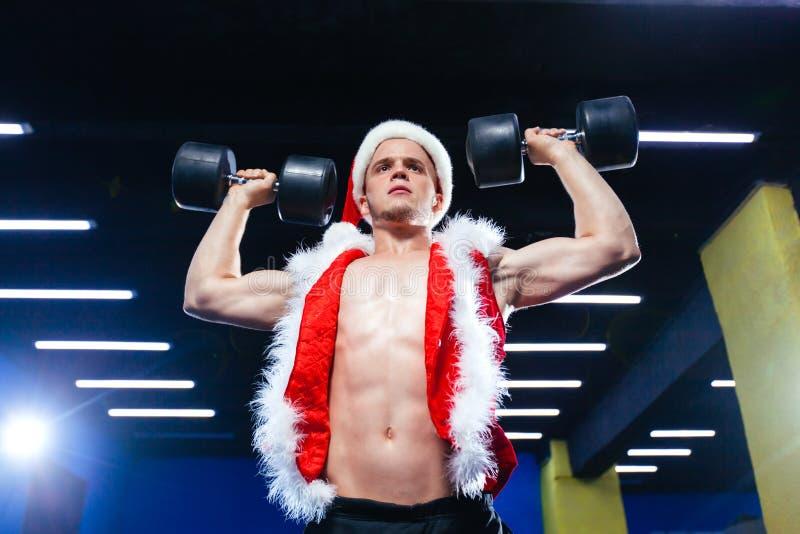 Wakacje i świętowania, nowy rok, boże narodzenia, sporty, bodybuilding, zdrowy styl życia - Mięśniowy przystojny seksowny Santa obraz stock