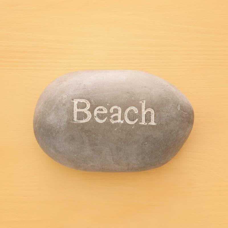 wakacje i lata wizerunek kamień z słowem WYRZUCAĆ NA BRZEG nad żółtym drewnianym tłem zdjęcia stock
