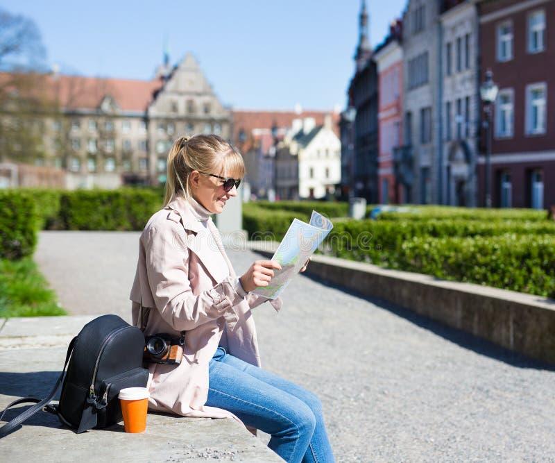 Wakacje i podróży pojęcie - kobieta w okularach przeciwsłonecznych z mapą, plecakiem i kamerą w starym miasteczku Tallinn, Estoni zdjęcia stock