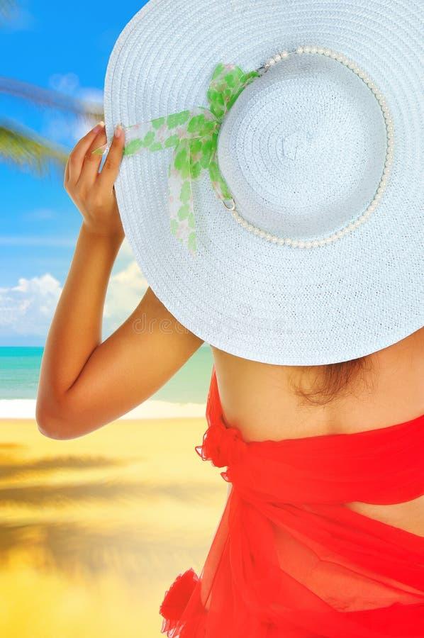 Wakacje kobieta na plaży z kapeluszem zdjęcie royalty free