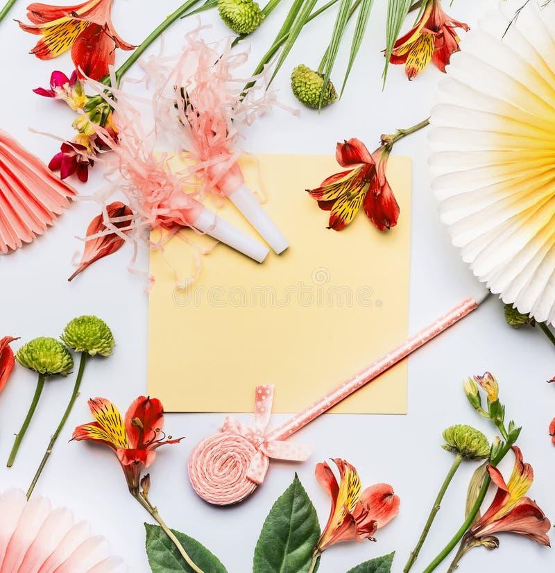 Wakacje letni gręplują z tropikalnymi palmowymi liśćmi, kwiaty, żółta pusta papierowa karta i partyjni akcesoria na białym deskto fotografia stock