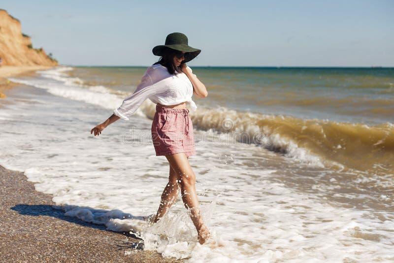 Wakacje pojęcie Szczęśliwa młoda kobieta w białym bieg i mieć zabawie z falami na pogodnej plaży koszula i kapeluszu Modnisia sch zdjęcia stock