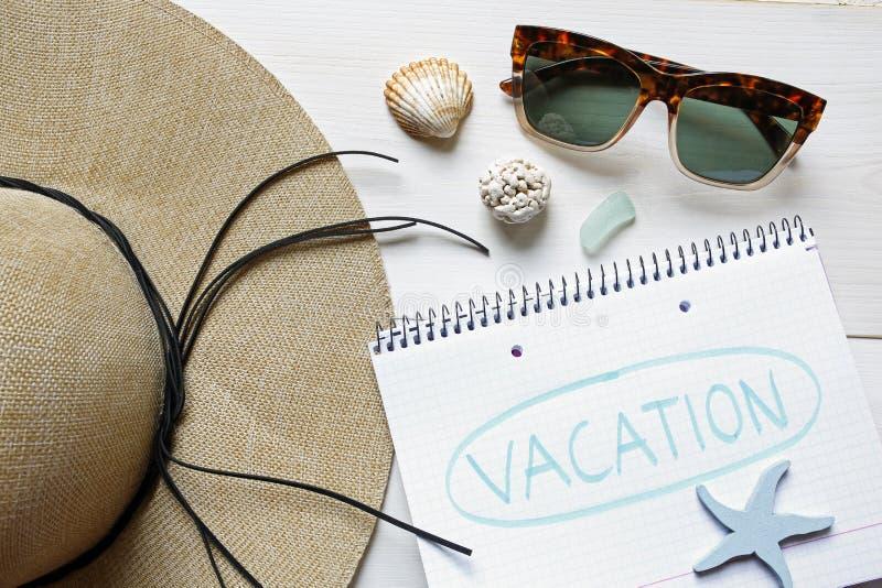 Wakacje pojęcia słomiany kapelusz, seashells, okulary przeciwsłoneczni i notatnik, obrazy stock